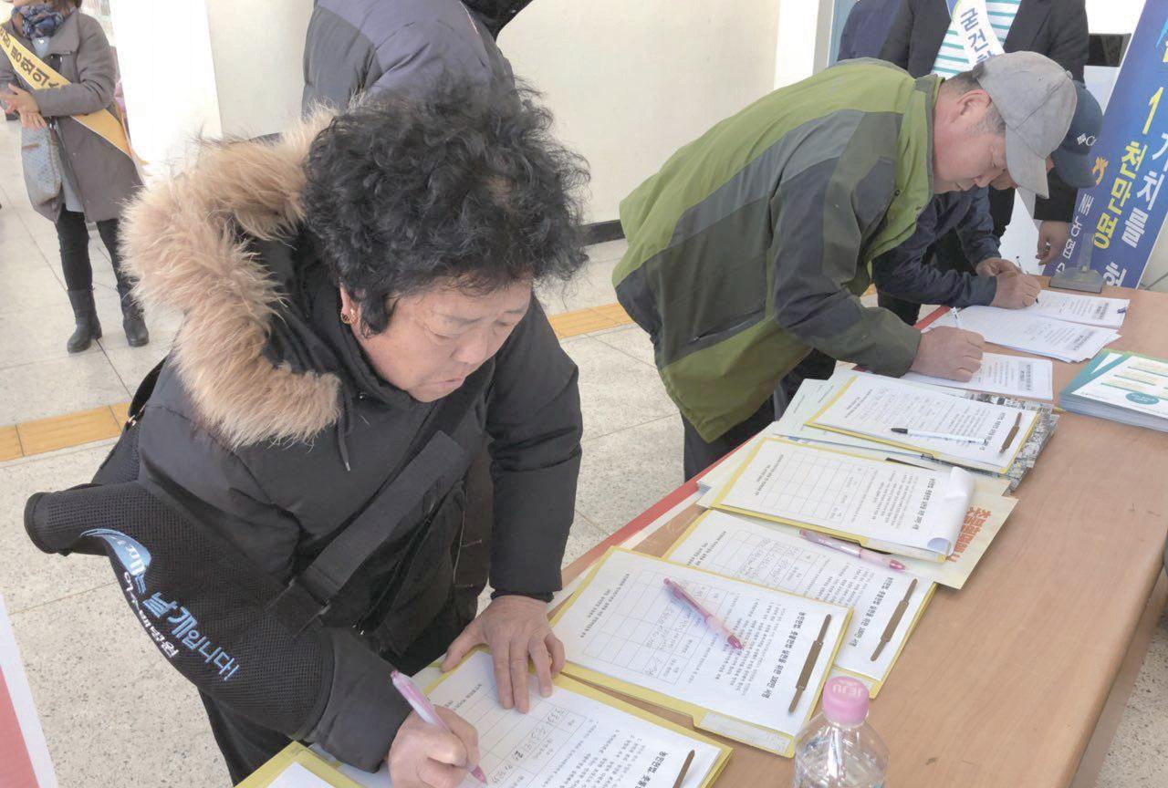 """""""헌법개정이 30년짜리 농사"""" 지난해 11월 순창 농업인의 날 행사에 참가한 농민들이 농민헌법 제정을 촉구하는 서명을 하고 있다. ⓒ한국농정신문"""