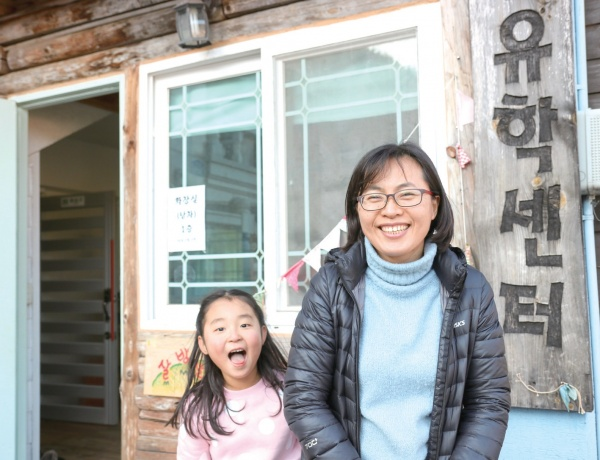 소호산촌유학센터 앞에 선 김미진 활동가. 산골캠프에 참여한 아이가 달려와 함께 섰다.