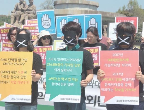 'GMO완전표시제 시민청원단'은 지난 5월 9일 청와대 분수대 광장 앞에서 기자회견을 열고, GMO 완전표시제 시행 촉구 국민청원에 대한 청와대 답변이 소비자의 눈과 입을 막고 있다는 의미의 퍼포먼스를 펼쳤다. ⓒ한국농어민신문