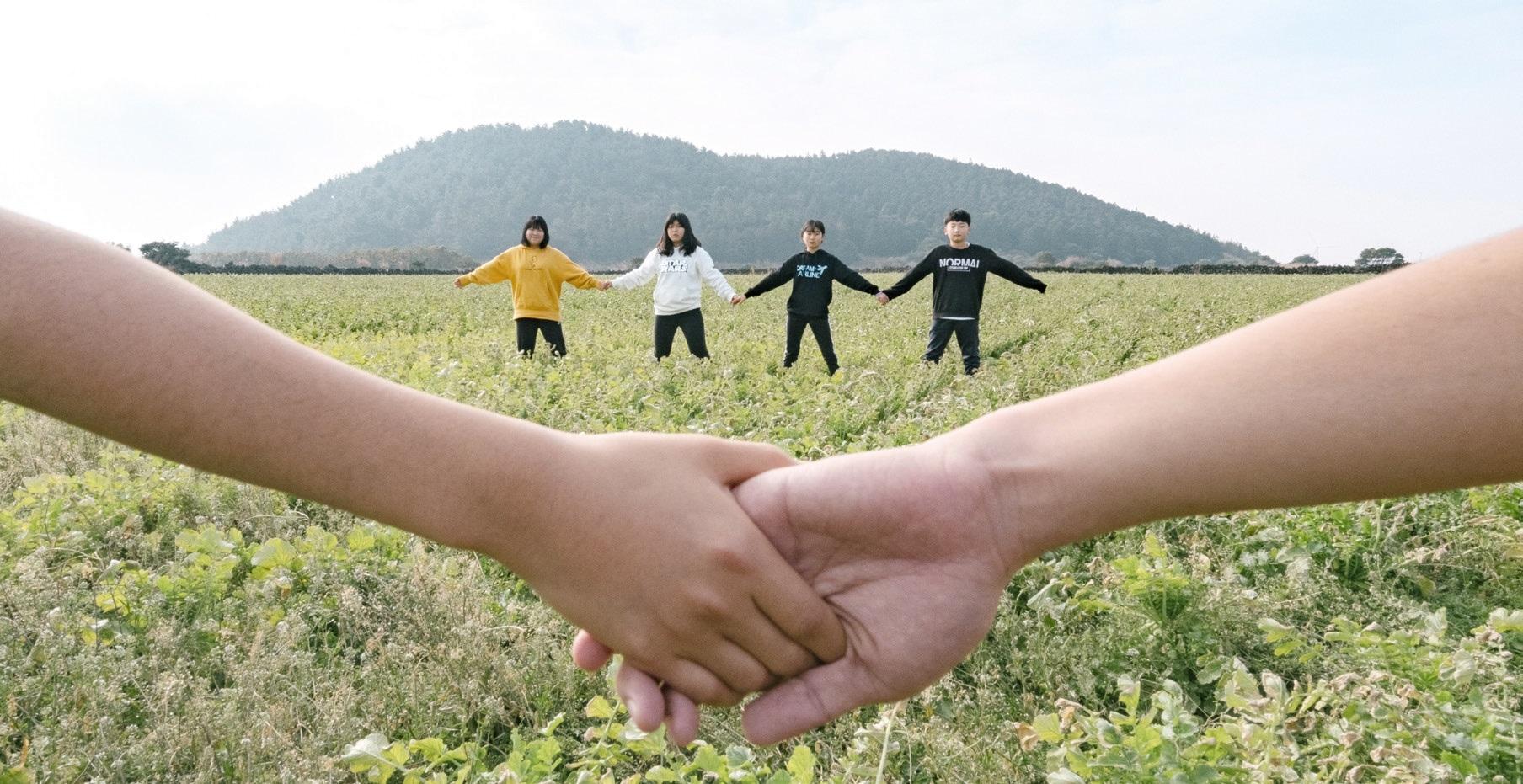 제주 보물섬학교 '아꼬운 방' 학생들이 서귀포 성산읍에 위치한 유건에오름을 찾아 손을 맞잡고 각자 바람을 말하고 있다.