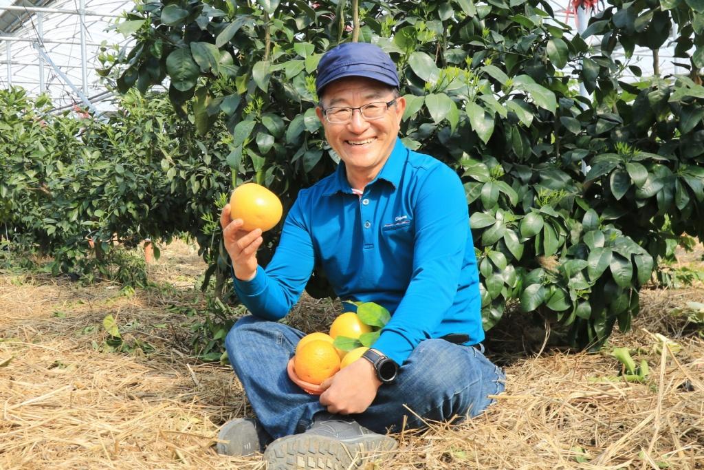 직접 재배한 유기농 자몽을 들고 환히 웃고 있는 김형신 대표.